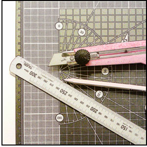 an image of cutting mat, knife, eraser and pencil